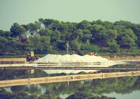 evaporation: Sea salt production. Salt evaporation pond with tractor and conveyor.