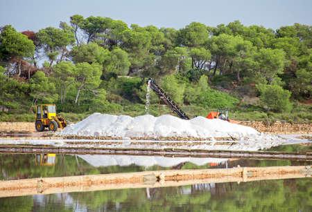evaporacion: La producci�n de sal de mar. Salina con el tractor y el transportador. Foto de archivo