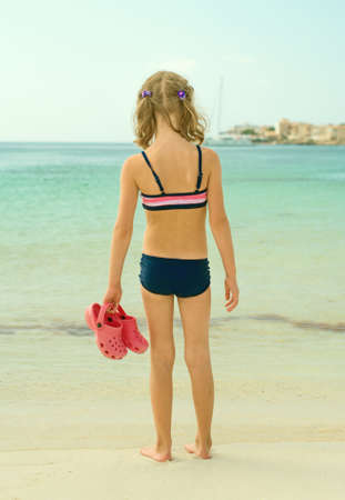 Little girl with flip flops standing on the beach. photo