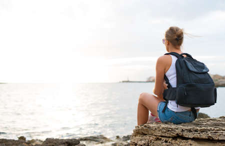 woman hiking: Woman with backpack relaxing near the sea. Stock Photo
