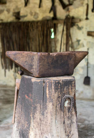 ancient blacksmith: Old anvil on the wooden stump.