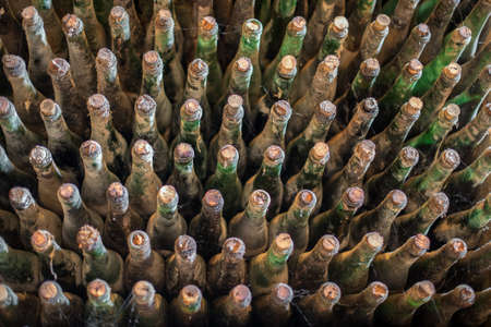 intoxicant: Pile of very old dusty wine bottles.