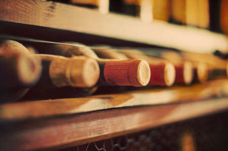 Wijnflessen gestapeld op houten rekken. Vintage effect.