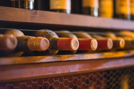 glass bottle: Wine bottles stacked on wooden racks.