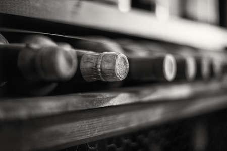 Wijnflessen gestapeld op houten rekken. Zwart-wit foto.
