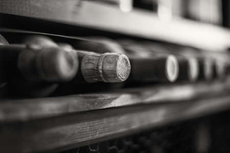 white wine: Wine bottles stacked on wooden racks. Black and white photo.