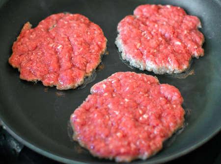 beefburger: Ground beef patties in the pan.