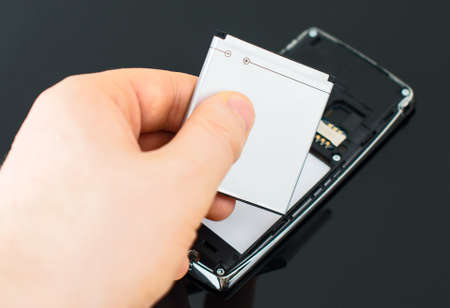 Male hand inserting battery to mobile phone.