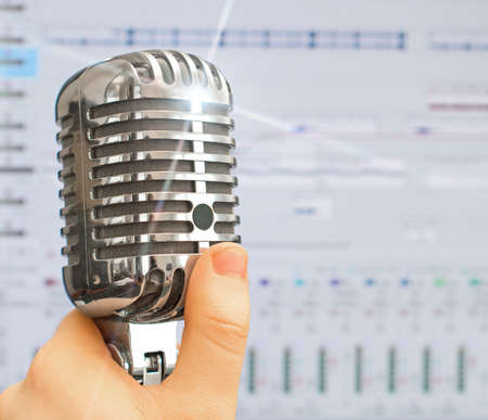 Hand holding retro microphone over recording software background. photo