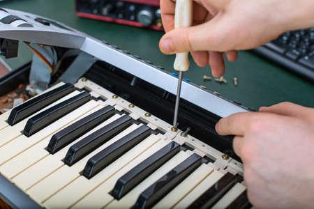 midi: Male hand fixing midi keyboard controller. Stock Photo