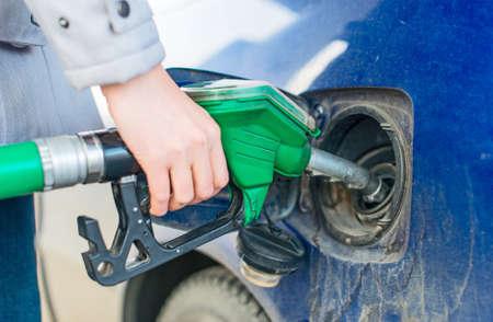 dirty car: Female hand refueling dirty blue car.