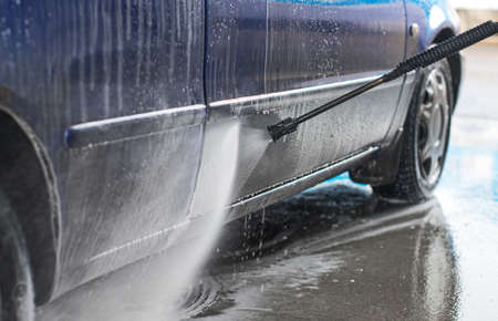 soaping: Blue car wash using high pressure water jet. Stock Photo