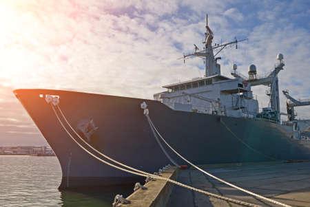 bollard: Naval auxiliary ship docked at the harbor.