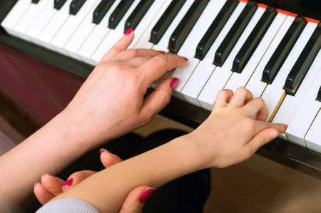 teaching children: Woman teaches the child to play the piano.