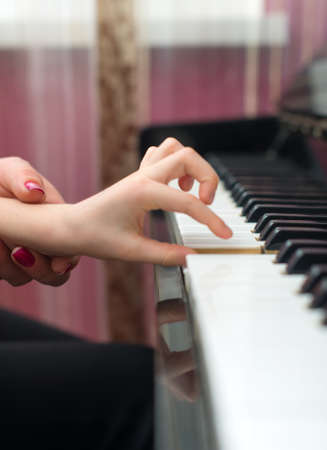 piano lesson: Woman teaches the child to play the piano.