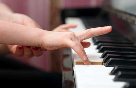 Žena učí dítě hrát na klavír.