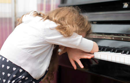 Child tired of learning the piano.