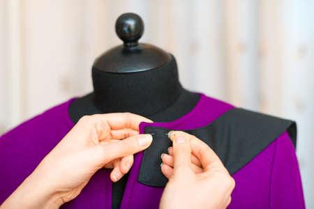 Female fashion designer working on mannequin. photo