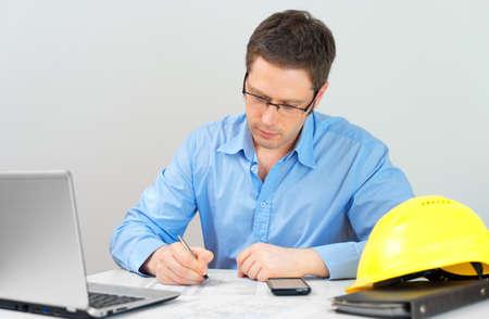 Arquitecto que trabaja en plan de la casa a su lugar de trabajo. Foto de archivo