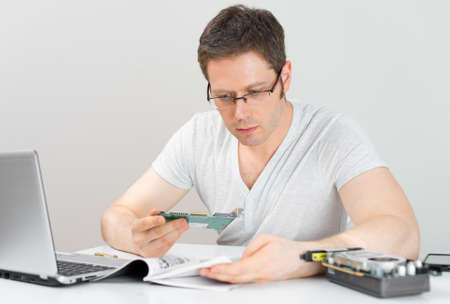 computer instruction: Male technician reading manual at his workplace. Stock Photo
