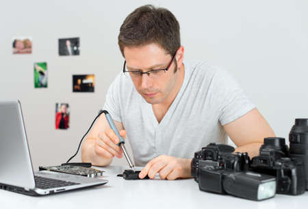 trigger: Photographer soldering wireless flash trigger at his workplace. Stock Photo