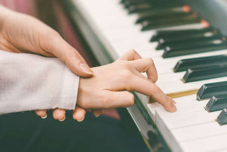 piano player: Woman teaching little girl to play the piano.