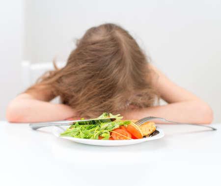 eten: Vermoeid meisje viel in slaap op de tafel.