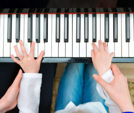 adult class: Woman teaching little girl to play the piano. Top view.
