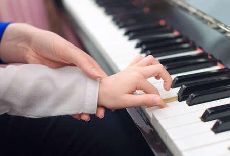 Donna insegnamento bambina a suonare il pianoforte.