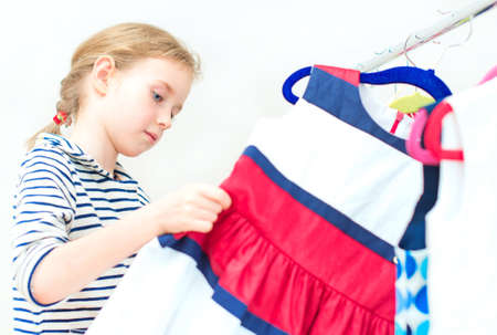 clothing store: Little girl choosing dress in clothing store. Stock Photo