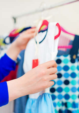 Woman's hand choosing child dress at clothing store. Stock Photo