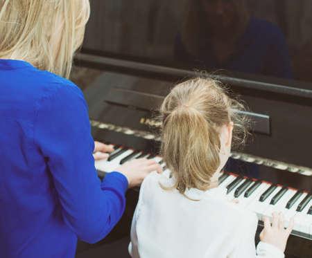 fortepian: Kobieta uczy dziewczynka gry na fortepianie. Widok z tyłu. Zdjęcie Seryjne