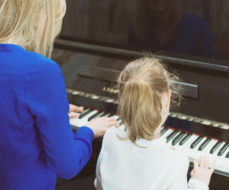 piano: Woman teaching little girl to play the piano. Back view. Stock Photo