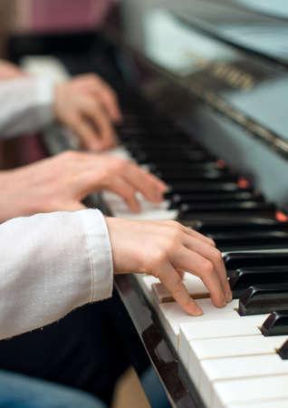 Woman teaching little girl to play the piano. Фото со стока - 40624041