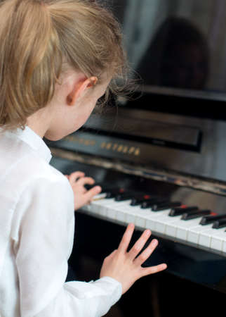 Little girl learning to play the piano. photo