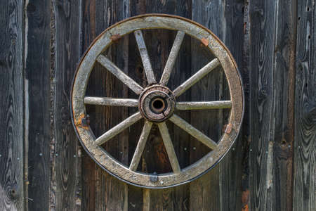 Old wooden carriage wheel hanging on the barn.