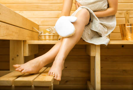 sauna: Woman relaxing in sauna. Massaging legs.