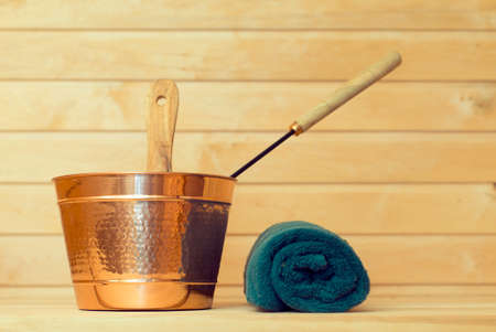sauna: Metal bucket and towel in sauna.
