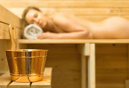 sauna nackt: Spa-Zubehör in der Sauna. Frau auf Hintergrund. Lizenzfreie Bilder