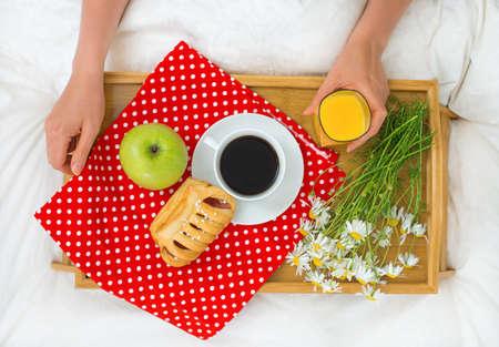 vaso de jugo: Desayuno en la cama. Café, bollo, manzana y jugo de naranja.