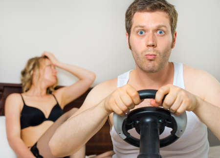 playing video game: Video game addiction. Man playing video game with steering wheel, upset woman on background. Stock Photo