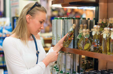Young woman choosing olive oil in grocery store. Stock Photo