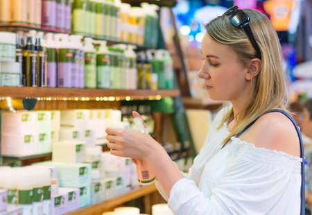 select: Young woman choosing cosmetic cream in beauty shop. Stock Photo
