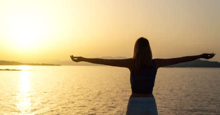 arms wide open: Woman with arms wide open at sunset.