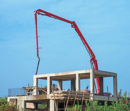 concrete pump: Trailer-mounted boom concrete pump at construction site.