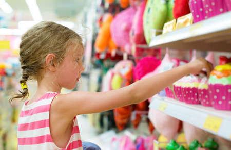 Klein meisje speelgoed te selecteren op de planken in supermarkt. Stockfoto