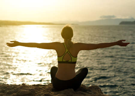 woman pose: Young woman practicing yoga near the sea.