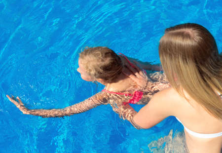 swimming pool woman: Woman teaching little girl to swim. Place for text. Stock Photo