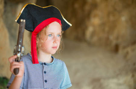 musket: Little girl in pirate costume with musket gun near the cave entrance. Place for your text.