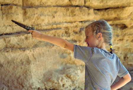 musket: Little girl with old musket gun aiming.